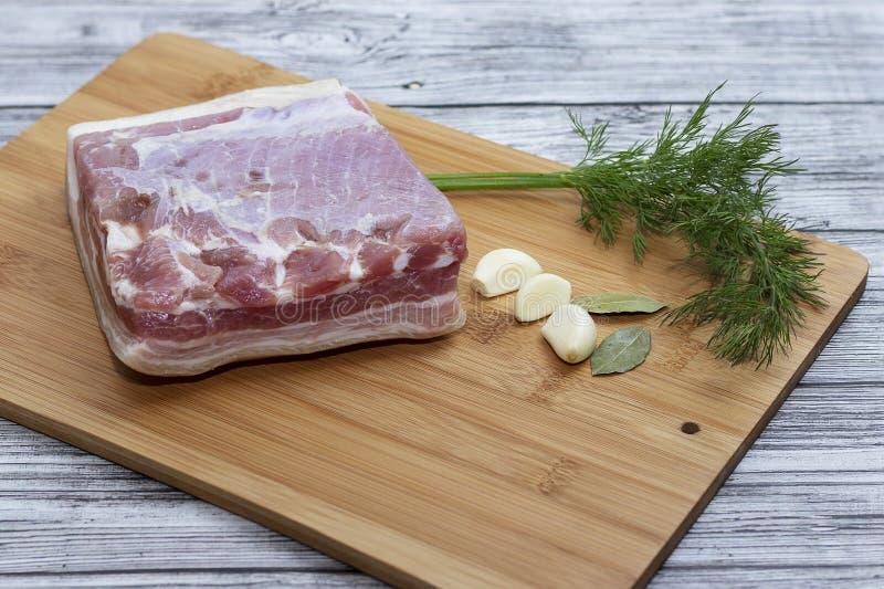 Een brok van varkensvleesbuik op de scherpe raad Sappige stukken van bacon met knoflook, peper en royalty-vrije stock foto