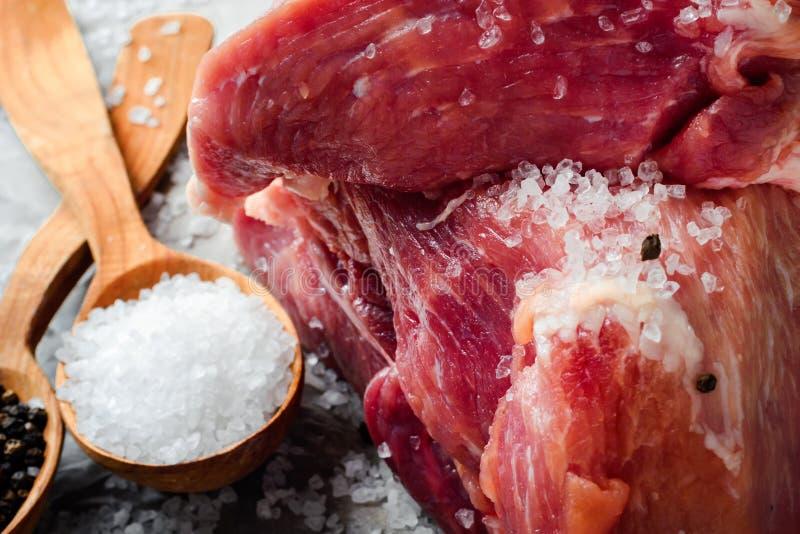 Een brok van vers sappig die vlees met zout wordt bestrooid Preparati royalty-vrije stock afbeelding