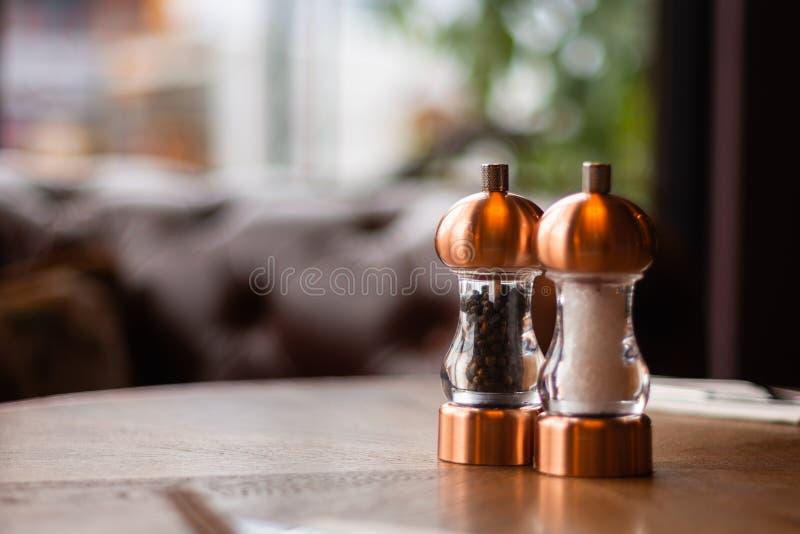 Een bronszout en de een peperschudbeker en molen zitten op een lijst binnen een Iers restaurant stock afbeeldingen