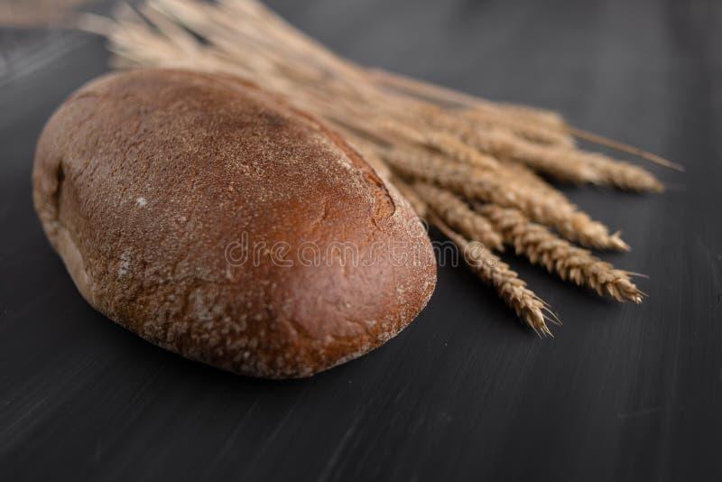 Een brood van donker brood op de lijst, naast het is tarwe in een oor royalty-vrije stock afbeeldingen