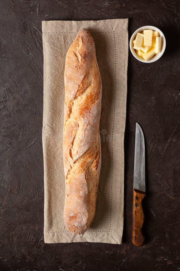 Een brood van eigengemaakte brood of baguette Met boter en mes Op een donkere geweven of bruine achtergrond stock foto's