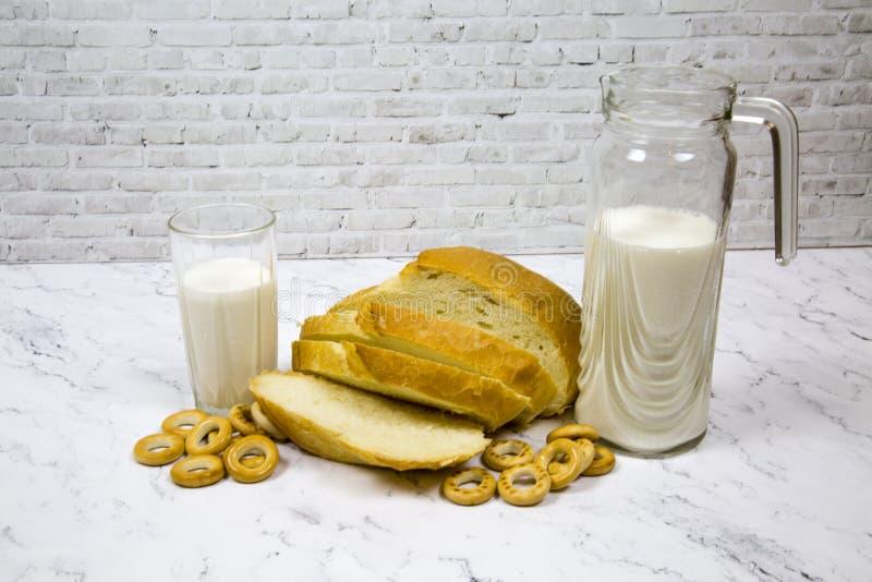 Een brood van wit die brood met een karafglas melk tegen een witte marmeren Raad wordt gesneden stock foto's