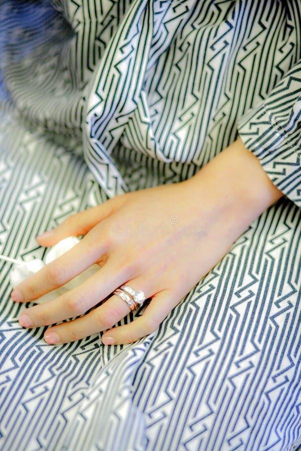 Een bruid met haar ring die een gestreepte patroonpyjama's dragen stock afbeeldingen