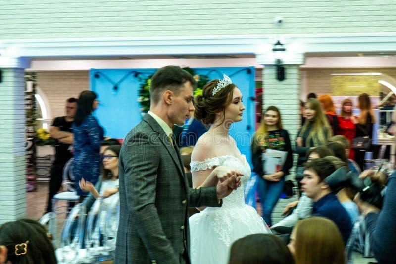 Een bruidegom en een bruid modelleren in huwelijkskleren die de gasten overgaan stock foto