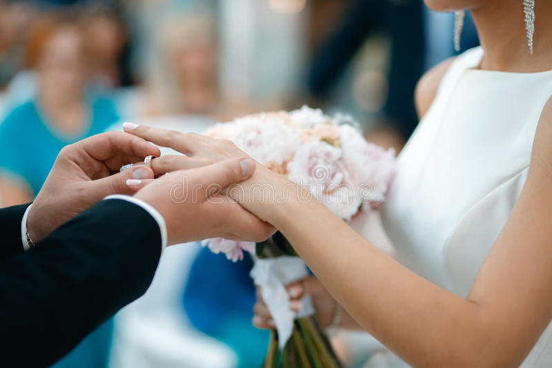 Een bruidegom zet een trouwring op de bruid` s vinger royalty-vrije stock foto's