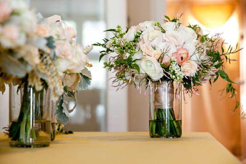 Een bruids die huwelijksboeket in een glaskruik vóór de huwelijksceremonie, Witte en roze bloemen op een lijst worden opgetekend royalty-vrije stock afbeeldingen