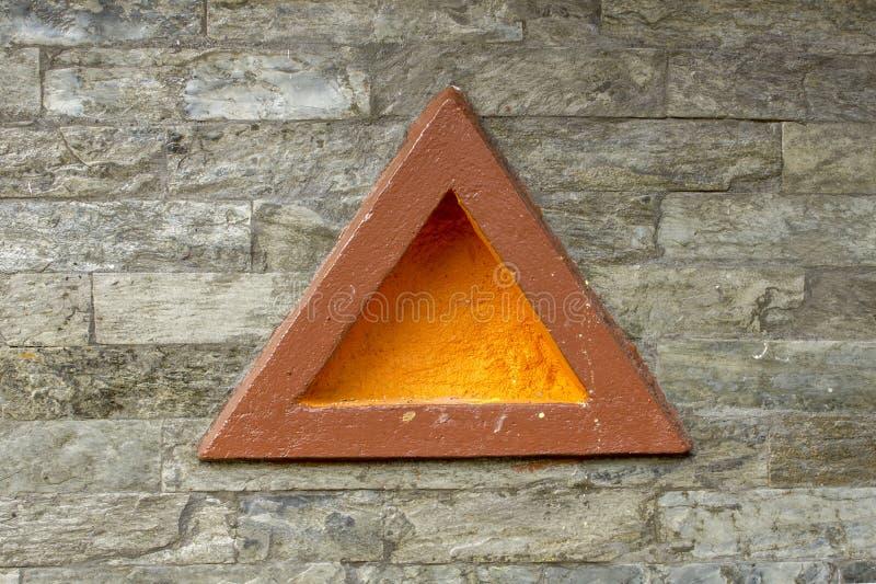 Een bruine driehoek met een geel centrum op een grijze bakstenen muur Geborstelde muurtextuur stock foto