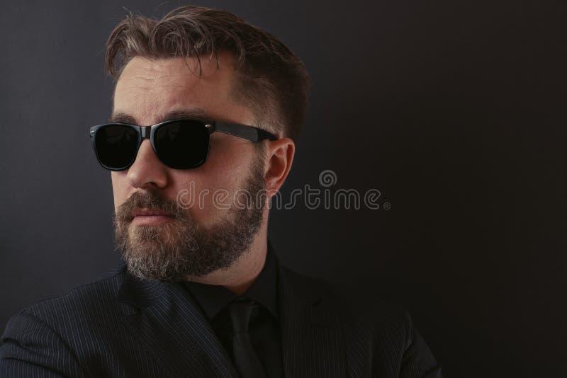 Een brutale mens met een baard en een modieus kapsel in een zwarte passen en zonnebril aan stock fotografie