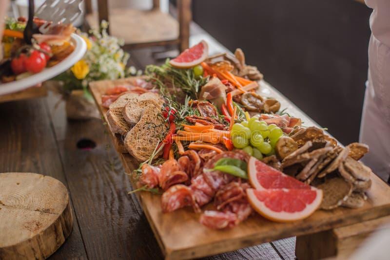 Een buffet van geassorteerde genezen ingelegd vlees, worsten, ham, vruchten, groenten, olijven, brood en saus voor een gebeurteni stock fotografie