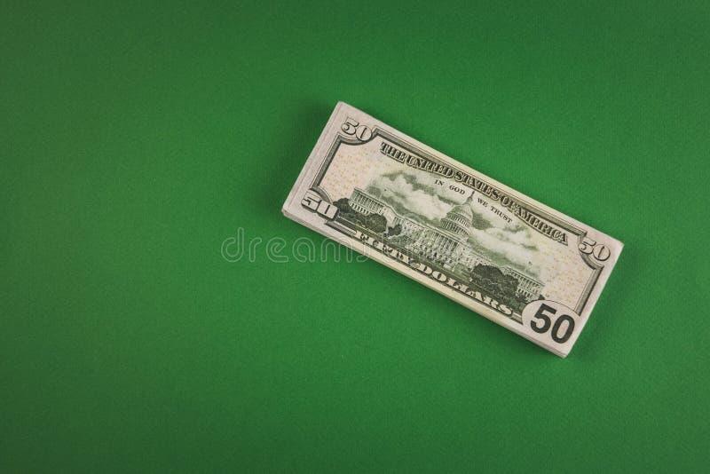 een bundel van geld in de vorm van vijftig dollarsrekeningen die op een groene achtergrond liggen stock foto