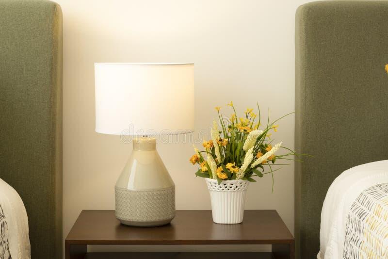 Een Bureaulamp, een vaas met bloemen over een bureau stock fotografie