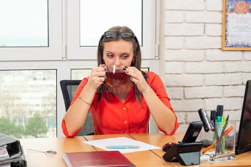 Een bureauwerknemer drinkt thee op het werk bij lunchtijd stock afbeelding