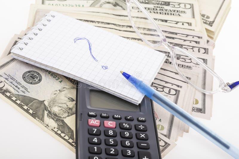 Een calculator en een notitieboekje met vraagteken op stapel van Amerikaanse dollars stock afbeelding