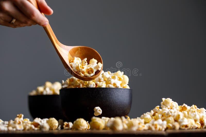 Een ceramisch komhoogtepunt van popcorn en een hand met een houten lepel holt het uit royalty-vrije stock afbeeldingen