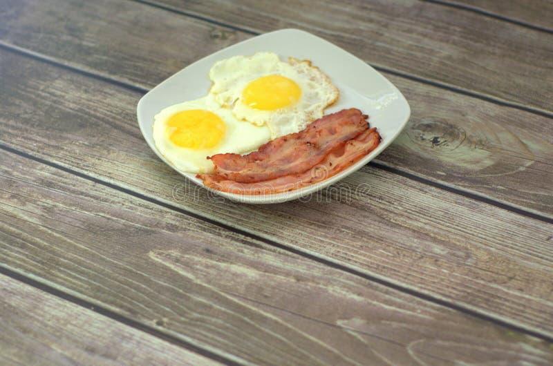 Een ceramische witte plaat met twee gebraden eieren en twee plakken van gebraden bacon bevindt zich op een houten lijst Close-up stock fotografie