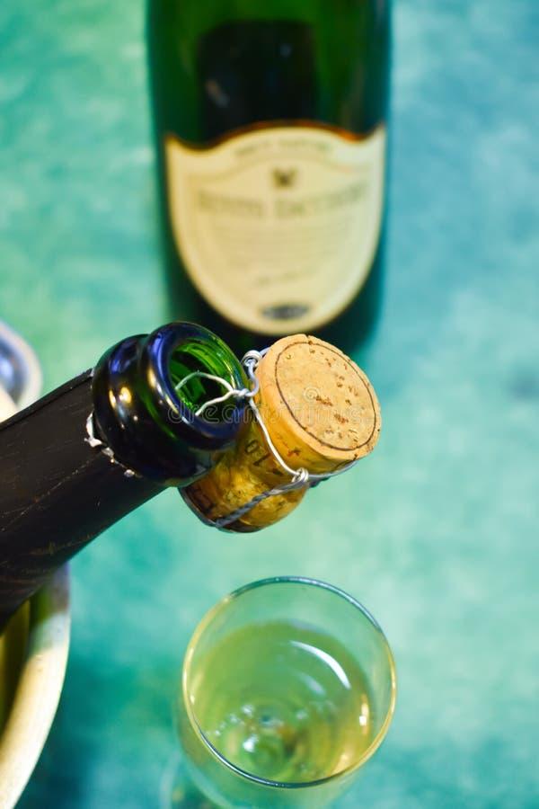 een champagnefles in een koude emmer met ijs en water, de cork holding van de mond die de scène, een kop met het vonken verfraaie royalty-vrije stock fotografie