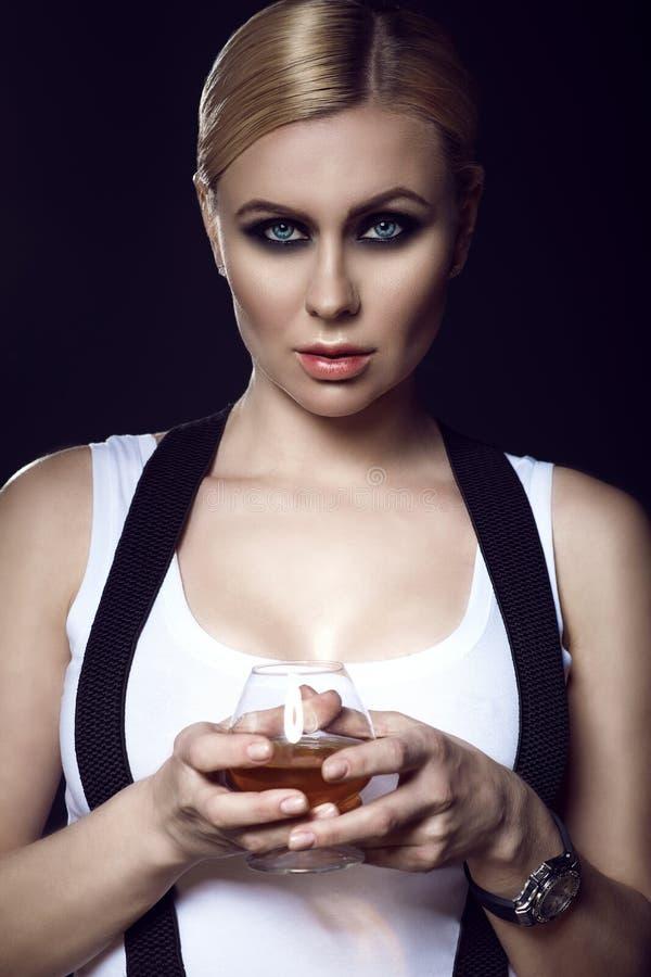 Een charmant blauw-eyed blond model die met getrokken achterhaar een glas brandewijn houden royalty-vrije stock foto's