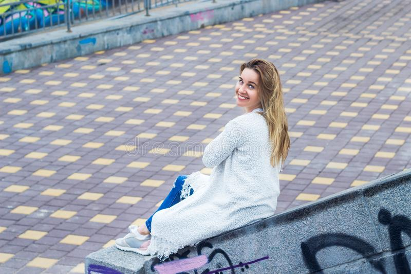 Een charmant die meisje zit op de bestrating op de straat in graffiti wordt geschilderd stock afbeeldingen