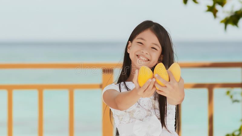 Een charmant Filippijns schoolmeisjemeisje in een witte kleding en een lang haar stelt positief met een mango in haar handen De z royalty-vrije stock foto's