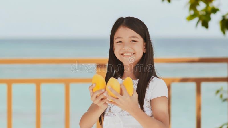 Een charmant Filippijns schoolmeisjemeisje in een witte kleding en een lang haar stelt positief met een mango in haar handen De z stock fotografie