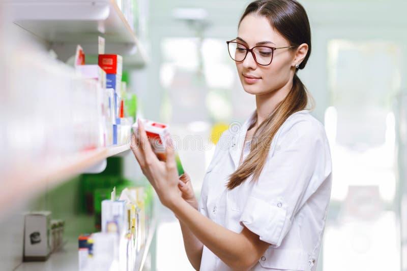 Een charmant glimlachend meisje met donkere haar en glazen, die een laboratoriumlaag dragen, neemt iets van de plank in modern royalty-vrije stock foto's