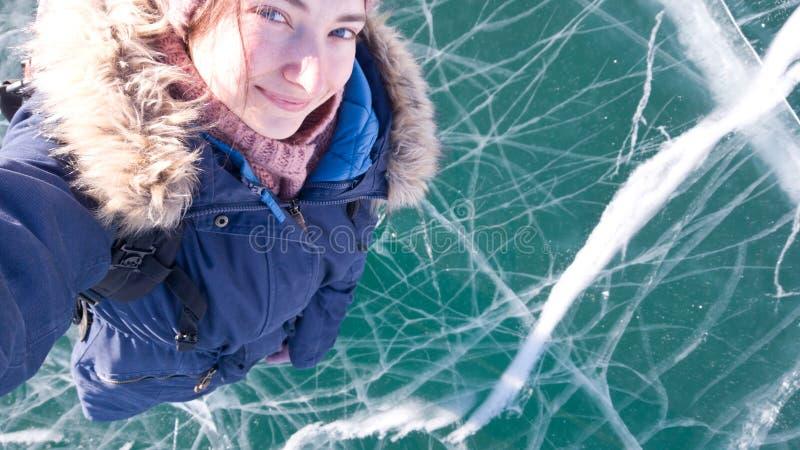 Een charmant meisje neemt een selfie op haar smartphone met haar hand die uit tegen de achtergrond van een helder bevroren meer B royalty-vrije stock afbeeldingen