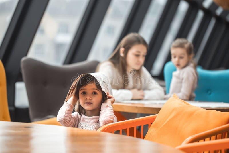 Een charmant meisje zat bij een houten lijst met een menu op haar hoofd in het restaurant stock foto