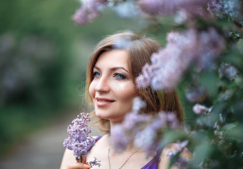 Een charmante mooie jonge zwangere vrouw in purpere violette kleding in een bloeiende lilac tuin bekijkt camera met tederheid stock foto's
