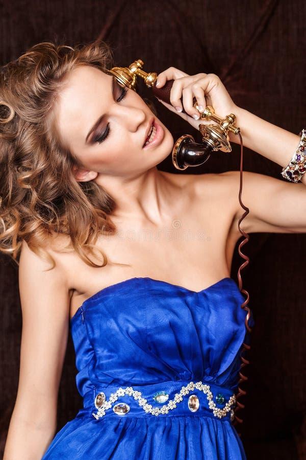 Een charmante vrouw met modieus krullend kapsel die een blauwe kleding dragen die op uitstekende oude telefoon in retro stijl spr royalty-vrije stock afbeelding