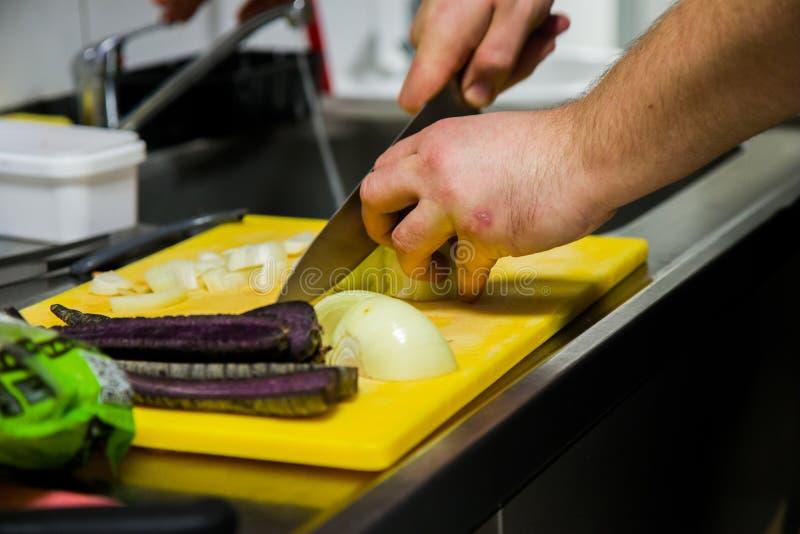 Een chef-kok scherpe ui in de keuken stock afbeeldingen