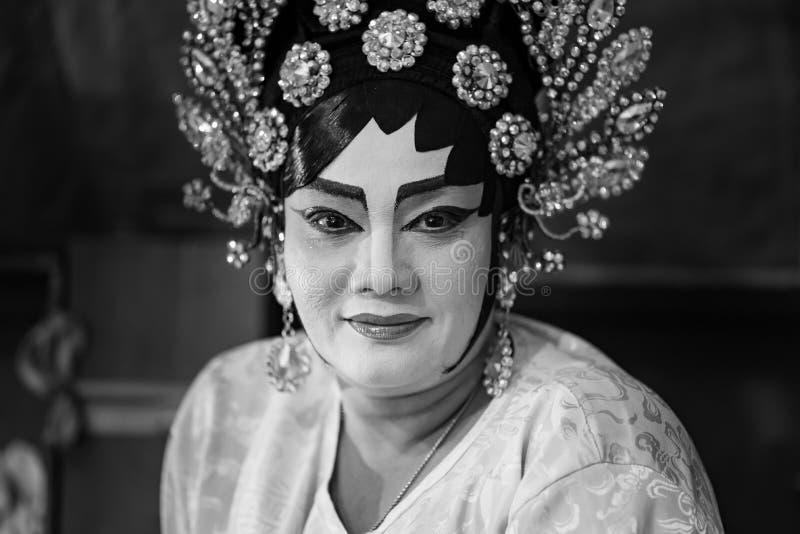 Een Chinees operaactrice het schilderen masker op haar gezicht vóór de prestaties bij coulisse bij belangrijk heiligdom in Bangko stock afbeeldingen