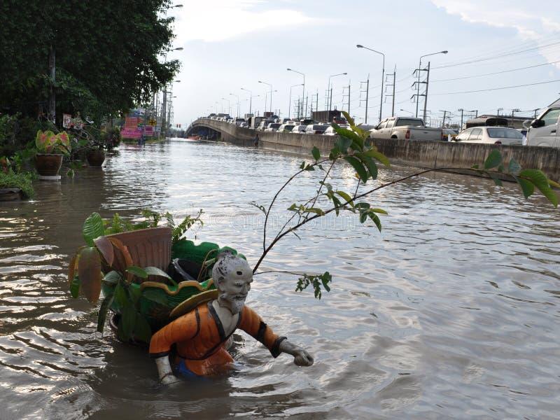 Een Chinees standbeeld is onderwater in een overstroomde straat van Pathum Thani in Oktober 2011 royalty-vrije stock afbeeldingen