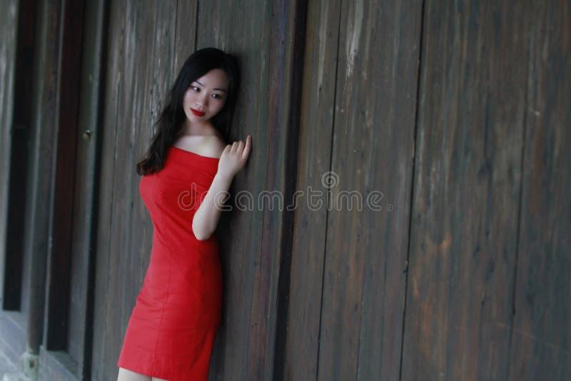 Een Chinese vrouw in rode kleding die op een woodern oude deur liggen royalty-vrije stock foto