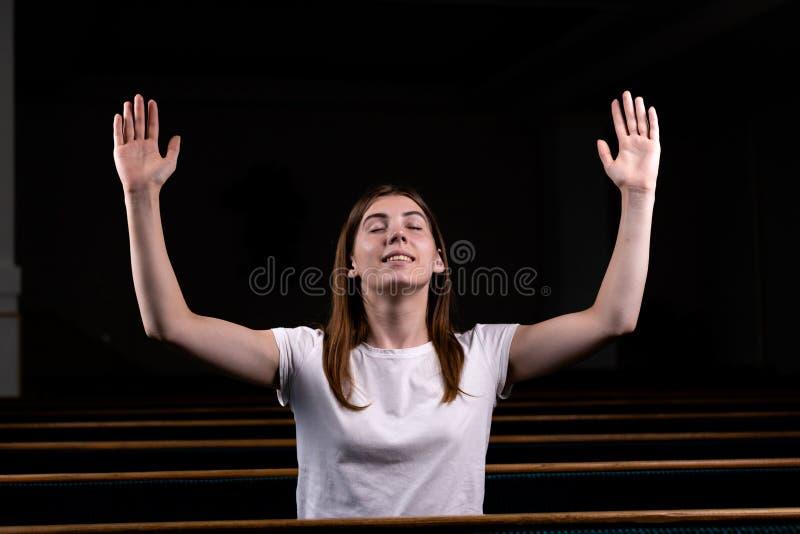 Een Christelijk meisje in wit overhemd is zit met zijn handen omhoog en gezicht en het bidden met bescheiden hart in de kerk stock foto