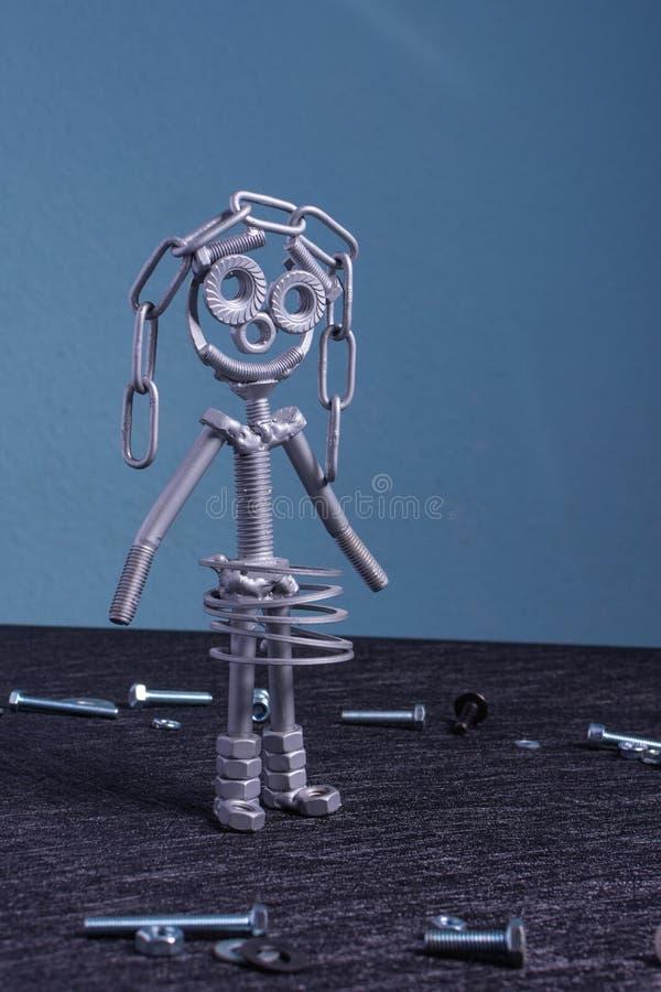Een cijfer van ??n kleine robot die van verscheidene bouten en noten wordt geassembleerd die zich in een verticale positie bevind stock afbeeldingen