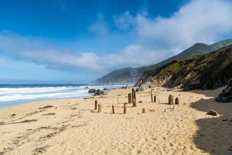Een cirkel van drijfhoutstukken plaatste in het gouden zand van een strand onder bergen en dramatische hemel en nevelige wolken royalty-vrije stock fotografie