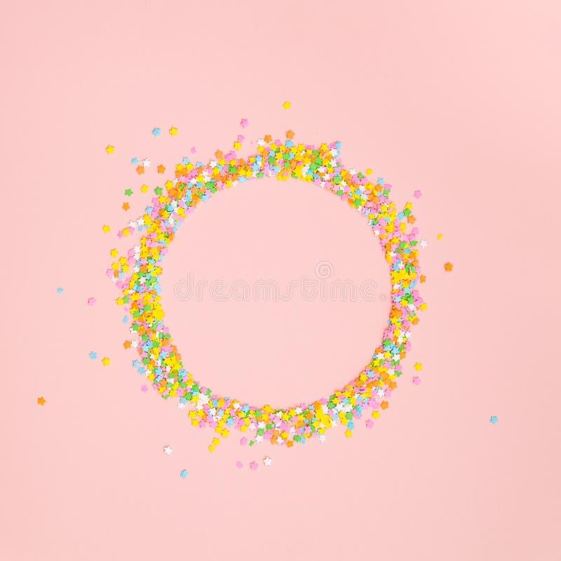 Een cirkel van gestalte gegeven pastelkleurster bestrooit op roze royalty-vrije stock fotografie