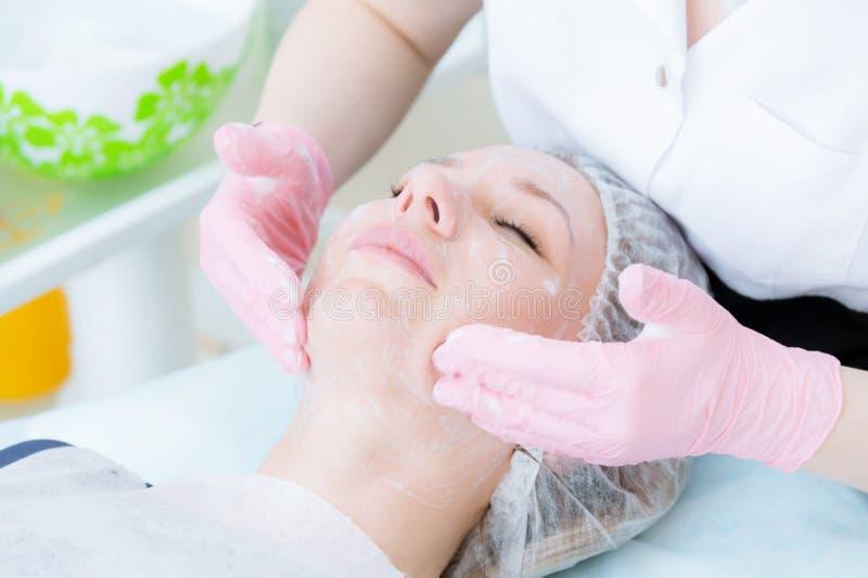 Een close-up van de het schoonmaken procedure in het bureau van de kosmetiek Het schoonmaken van de huid met schuim Mooi meisje b royalty-vrije stock afbeeldingen