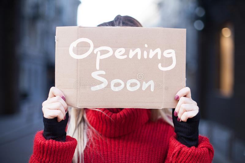 Een close-up van de kartontablet met de inschrijving die ?spoedig ?in de handen van een jonge vrouw in een rode sweater openen stock afbeelding