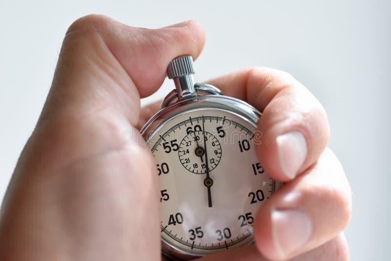 Een close-up van een geïsoleerde hand drukt de chronometerstarter in de sport, metingen, metrologie royalty-vrije stock afbeeldingen