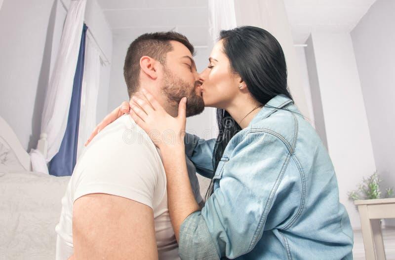 Een close-up van een gelukkig paar die en in de slaapkamer koesteren kussen royalty-vrije stock afbeeldingen