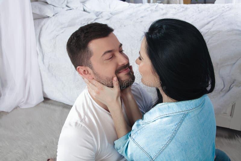 Een close-up van een gelukkig paar die en in de slaapkamer koesteren kussen stock afbeelding