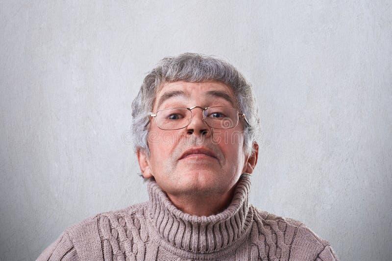 Een close-up van grappige grootvader in glazen die gelukkig door oogglazen kijken die pret hebben Een bejaarde die geheimzinnige  royalty-vrije stock afbeelding