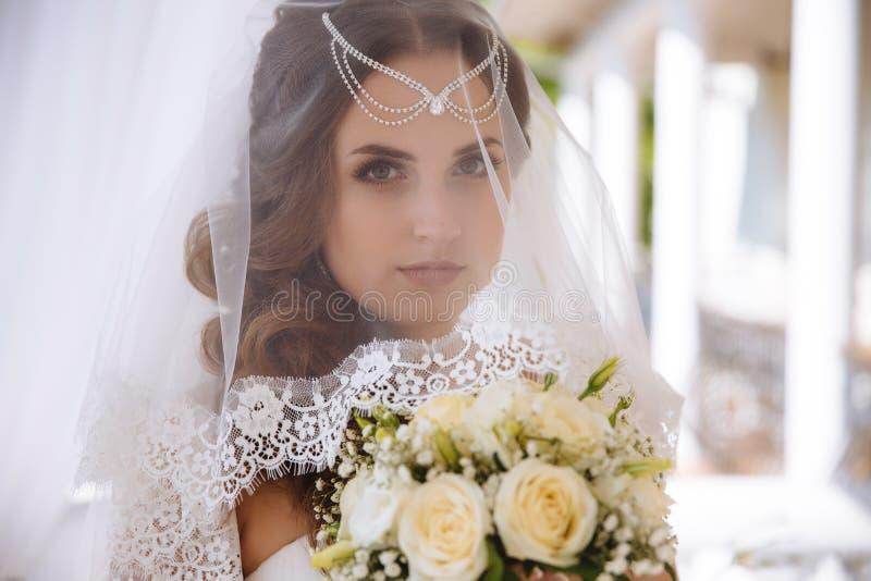 Een close-up van het gezicht van een groen-eyed bruid in een versluierde sluier, haar haar is verfraaid met lalatic, makiia van n stock afbeelding