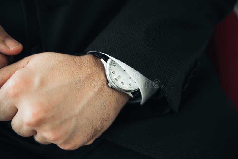 Een close-up van een horloge met leerarmband op man hand royalty-vrije stock afbeelding