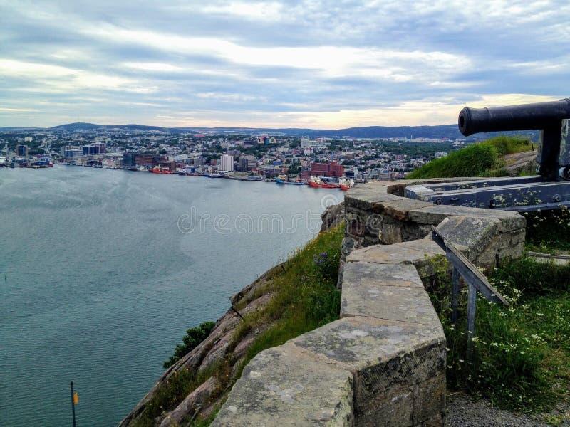 Een close-up van een kanon die de haven in St John Newfoundland met de stad en haven op de achtergrond overzien stock foto