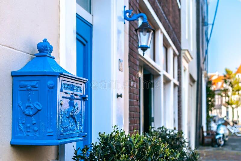 Een close-up van een mooie diepe blauwe Nederlandse die brievenbus met een bas-hulp met een straatmening bij de achtergrond wordt stock foto's