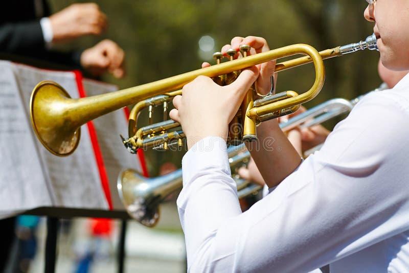 Een close-up van verscheidene trompetters die in een fanfarekorps spelen stock afbeelding