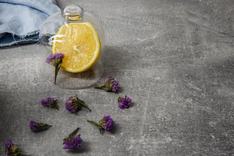 Een close-upbeeld van een mooie samenstelling op een grijze achtergrond Heldere citroen, blauwe stof en droge bloemblaadjes van p royalty-vrije stock fotografie