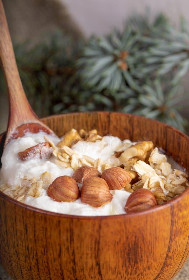 Een close-updeel van houten kom met eigengemaakte yoghurt met gerolde haver en noten royalty-vrije stock foto
